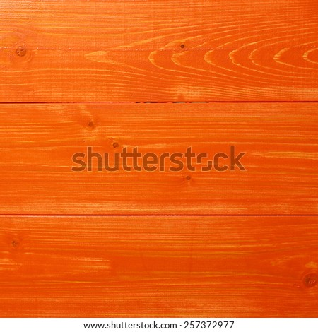 Orange paint coated wooden pine boards lying in a row as a close-up background composition - stock photo