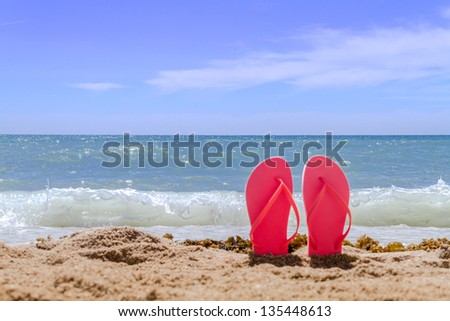 Orange pair of flip flops sticking up on a sandy beach with water and waves crashing on the beach - stock photo