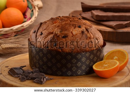 Orange panettone bread and ingredients on rustic wood ambient.Panetone and ingredients.Traditional italian christmas food. - stock photo