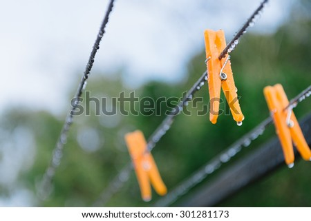 orange pegs on clothesline in the rain, it's a dryer day - stock photo
