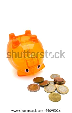 Orange piggy bank upside down with some coins in the front - stock photo