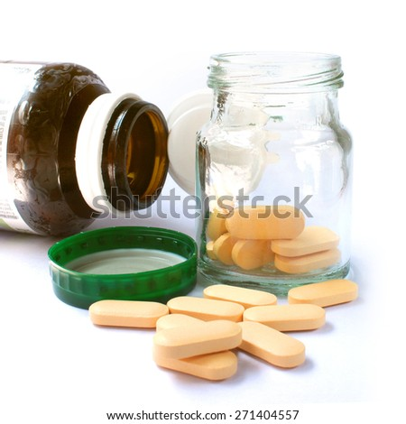 Orange pill with brown bottle. - stock photo