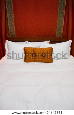 Orange pillow on big bed with white sheets.  Draped behind wood headboard is red fabric. - stock photo