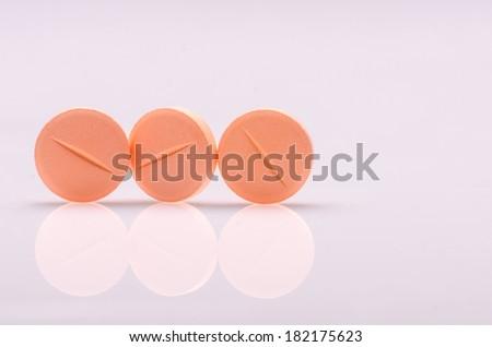 Orange pills on white surface  - stock photo