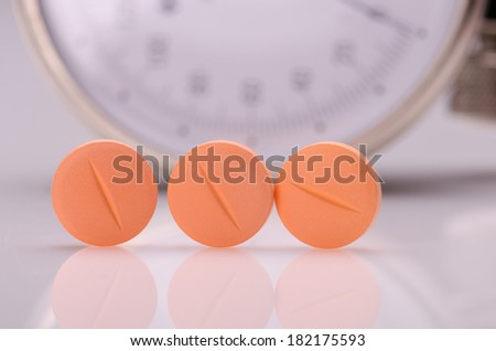 Orange pills on white surface against the dial of the tensiometer  - stock photo