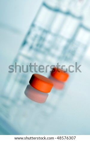 Orange pills with vials in the background. shallow dof - stock photo