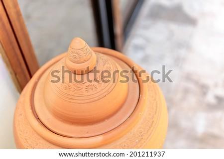 Orange pitcher earthenware is tradition of Thailand wood door and concrete floor have sunlight background blur - stock photo
