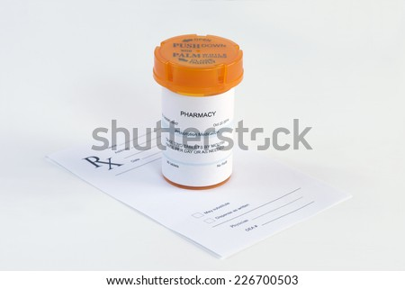 Orange prescription bottle on blank prescription. - stock photo