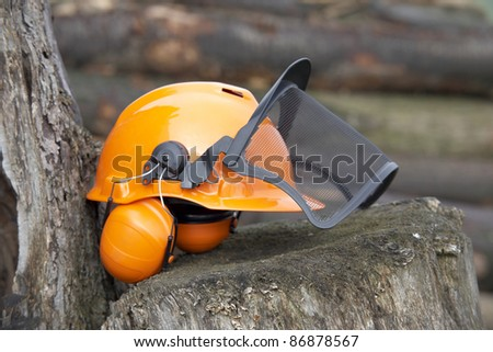 orange protective helmet with ear- and face- protection.  Outdoor shot in woody ambiance - stock photo