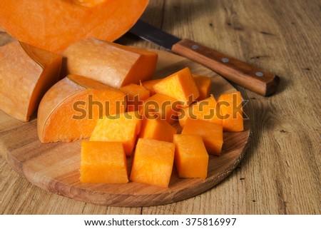 Orange pumpkin cut on a wooden board. - stock photo