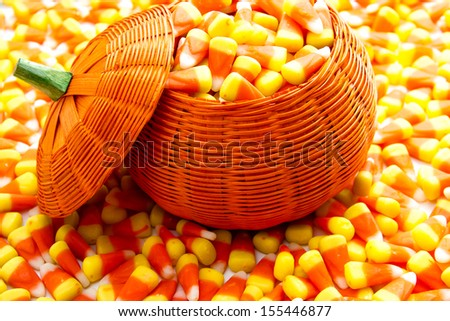 Orange pumpkin wicker basket fill with candy corn - stock photo