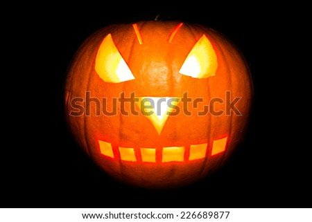 Orange pumpkin with backlit face carved for Halloween isolated on black - stock photo