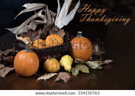 Orange Pumpkins, small gourds and Indian corn set on a table as a Thanksgiving decoration - stock photo