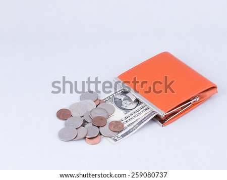 orange purse with five and one dollars and coins isolated on white cloth - stock photo