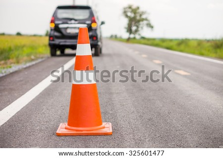 Orange rubber traffic cone on country road. It is used for warning to broken down car on country road, Thailand. - stock photo