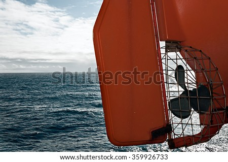 Orange Safety Lifeboat On Ferry Deck Over The Sea - stock photo