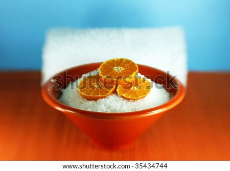 Orange-scented aromatherapy bath salts with slices of tangerine and a spa towel - stock photo