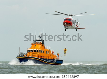 orange sea rescue boat at sea off south coast of Britain man being winched to emergency rescue helicopter - stock photo