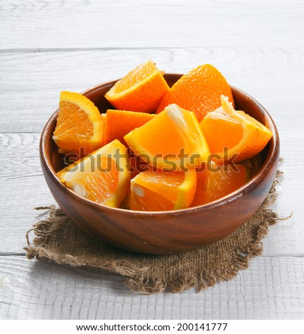 Orange segments in a wooden cup on an old fabric. On a wooden background. - stock photo