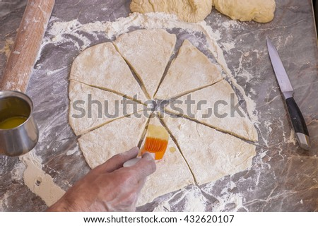 Orange silicone brush for food is lubricated dough - stock photo