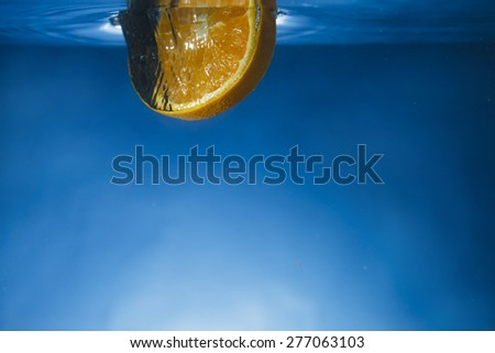 Orange slice dropped in crystal clear water just breaking the surface with blue gradient background - stock photo
