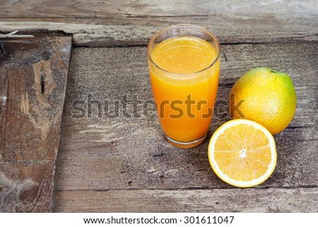 Orange sliced in half and thinly sliced and fresh orange juice in glass on old table wood - stock photo
