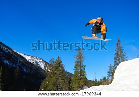 Orange snowboarder jumping high in the air - stock photo