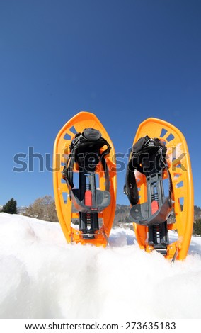 Orange SNOWSHOES for excursions on the snow in the mountains - stock photo