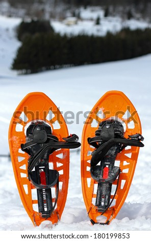 Orange snowshoes for walking on the soft snow - stock photo