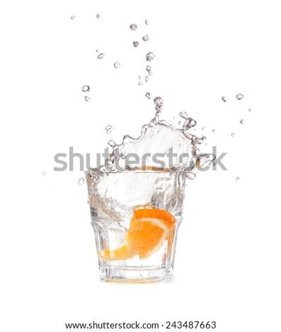orange splashing into glass of water on white background - stock photo