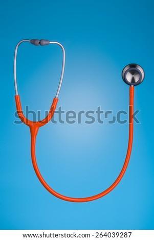 Orange stethoscope isolated on blue background - stock photo