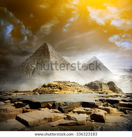 Orange storm clouds and fog over egyptian pyramids - stock photo