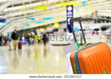 Orange suitcase with blank label at airport. - stock photo