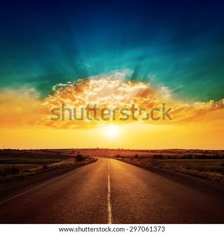 orange sunset and asphalt road to horizon - stock photo