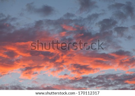 Orange sunset behind bright lit clouds, blue sky over northern California. - stock photo