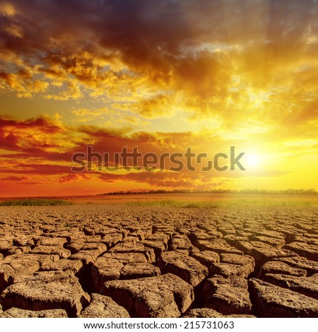 orange sunset in cloudy sky over desert - stock photo