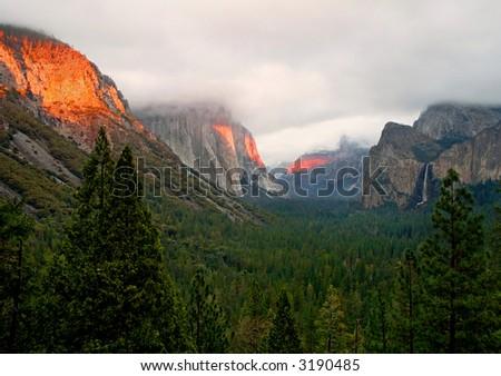 Orange sunset light across the mountains in Yosemite Valley - stock photo