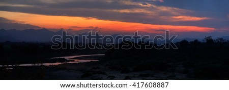 Orange sunset on the border of Kruger national park with Crocodile river mirroring colorful sky against mountains silhouettes in background.  Pestana Kruger Lodge, South Africa. - stock photo