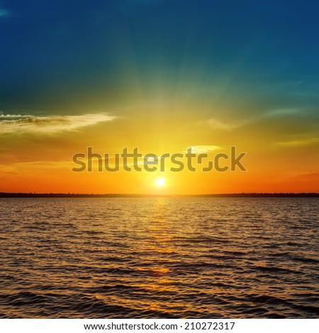 orange sunset over dark water - stock photo