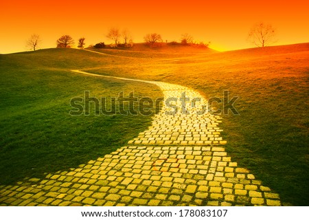 orange sunset over hill with paved walkway - stock photo