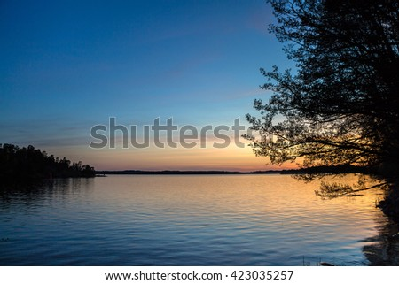 Orange sunset over lake with big tree silhouette on the edge and forest on the other opposite shore. Beautiful landscape with sunset over the river and rippling water. Gradient blue, purple and yellow - stock photo