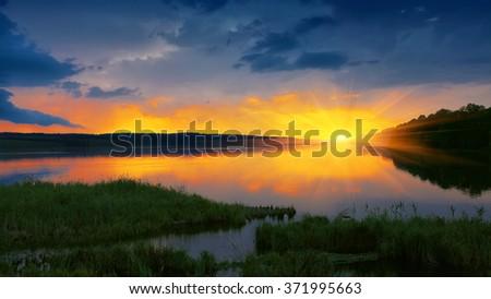 orange sunset over river. Dramatic sky. Twilight - stock photo