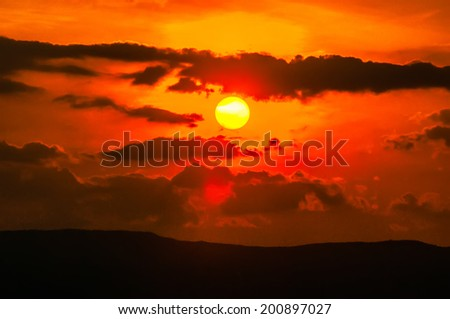 orange sunset sky and clouds over mountain valley - stock photo