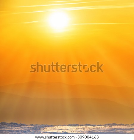 Orange sunset with big sun and sunrays over winter mountains - stock photo