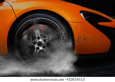 Orange super sport car from side with detail on spinning wheel, smoking and doing burnouts on a dark background - stock photo