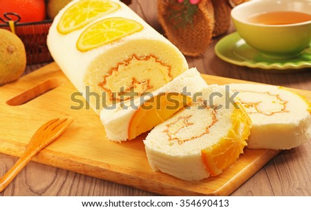 Orange swiss roll on the wooden cutting board    - stock photo