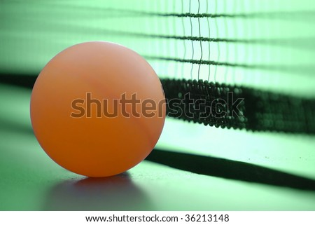 Orange table tennis ball on green table with net - stock photo