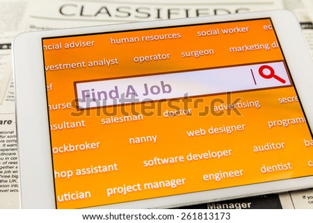 "Orange tablet screen fill with career words. Internet website for online job search having wording ""find a job"" in search engine box. Blur classifieds ads on background. Top view image. - stock photo"