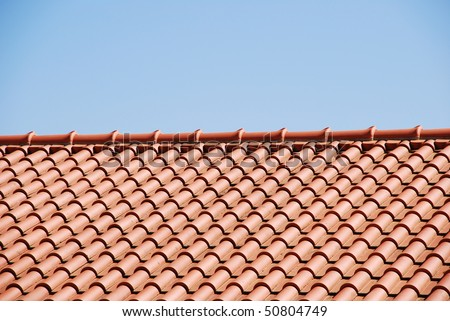orange tiles on the roof of a house against blue sky background - stock photo