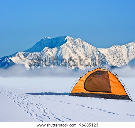 orange touristic tent before ice wall - stock photo